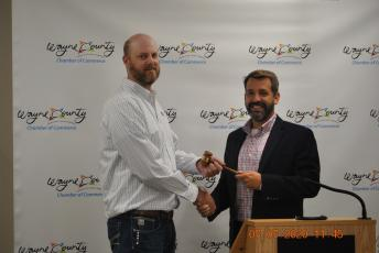 Justin Franks, left, accepts the Wayne County Chamber of Commerce gavel from Bryan Griffis.