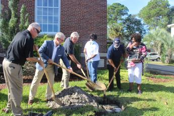 At the conclusion of Saturday's celebration of the Jesup Sesquicentennial, a time capsule was buried in front of Jesup City Hall. From left, Commissioner Ray House, Mayor David Earl Keith, City Manager Mike Deal, and Commissioners Shirlene Armstrong and Don Darden toss in the first ceremonial shovelfuls of dirt; with them is city clerk Rose Marcus.