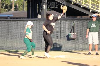 First baseman Krysie McKinzie has to jump for a throw from catcher MacKenzie Kagee in a pick-off attempt of a Lady Gator.