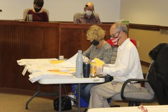 Beverly Leaphart and John Stanton count presidential votes on paper ballots. In the background are Probate Judge Tammy Thornton, who oversees elections in Wayne County, and Ed Whidden, who oversees the county government's information technology.