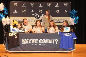 MacKenzie Kagee, center, signs a national letter of intent to play softball at College of Coastal Georgia. She is joined on the front row by her family, from left, Jaxton Kagee, Ryan Kagee, Morgan Mercer and Gracie Kagee. In back is varsity head softball coach Jessica Johnson.