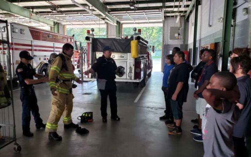 Jesup Fire Department firefighters Tyler Walker, Joshua Brothers and John Westberry demonstrate the process of donning protective gear for firefighting to a group of students who visited the fire station. The department has an active program to inform and motivate students about the opportunities for professional and volunteer firefighting in the county.