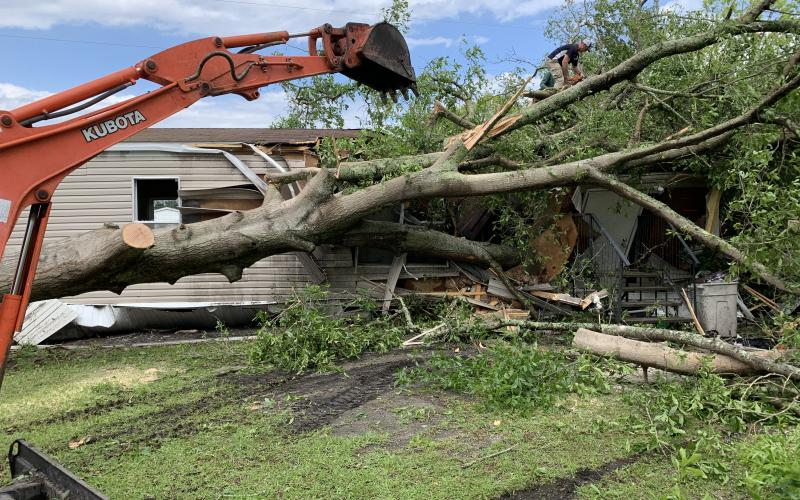 Volunteers with chain saws and heavy equipment were out in force in Odum Monday to clear up damage from a tornado. Many residences, such as this one on Issac Street, suffered extensive damage.